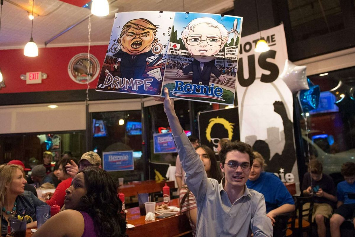 Supporters of Democratic Presidential hopeful Bernie Sanders holds a sign during a Super Tuesday voting watch party in support of Bernie Sanders in St Louis on March 15, 2016.