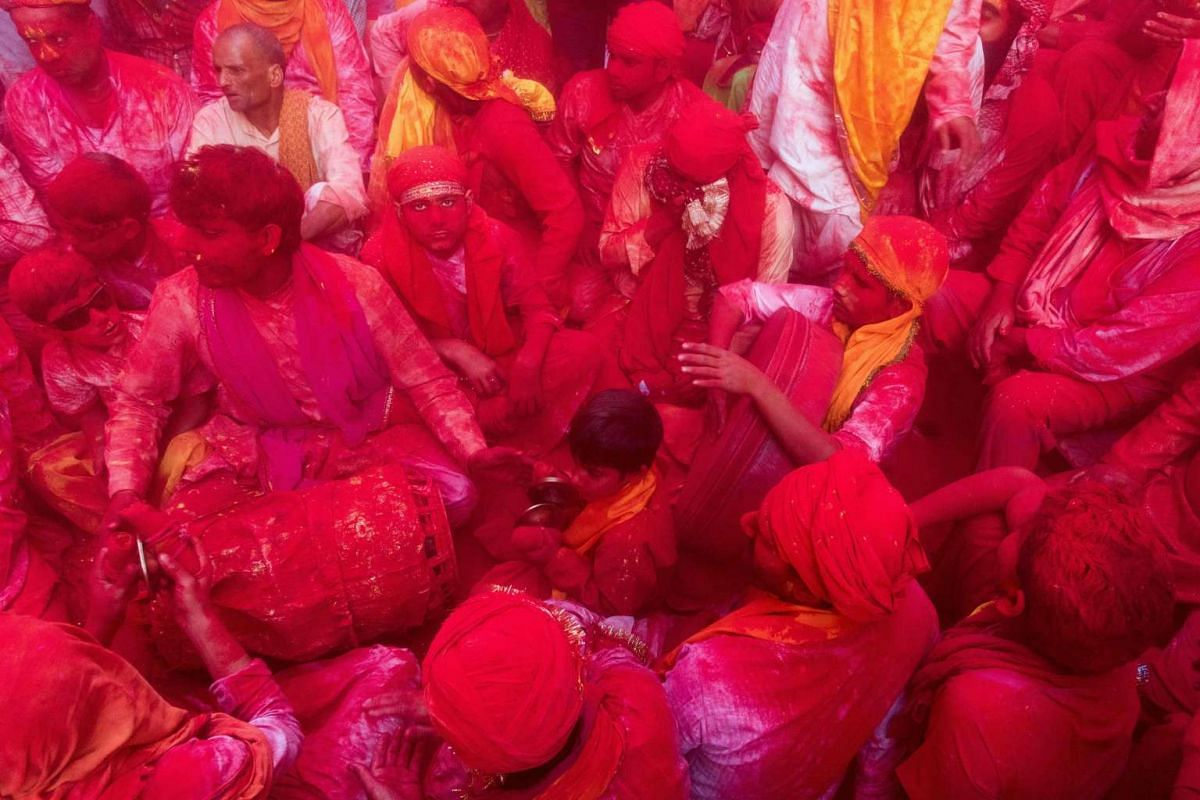 Indian villagers are covered with coloured powder during the Lathmar Holi festival at the Radha Rani temple in Barsana, some 130kms from New Delhi on March 16, 2016. PHOTO: AFP