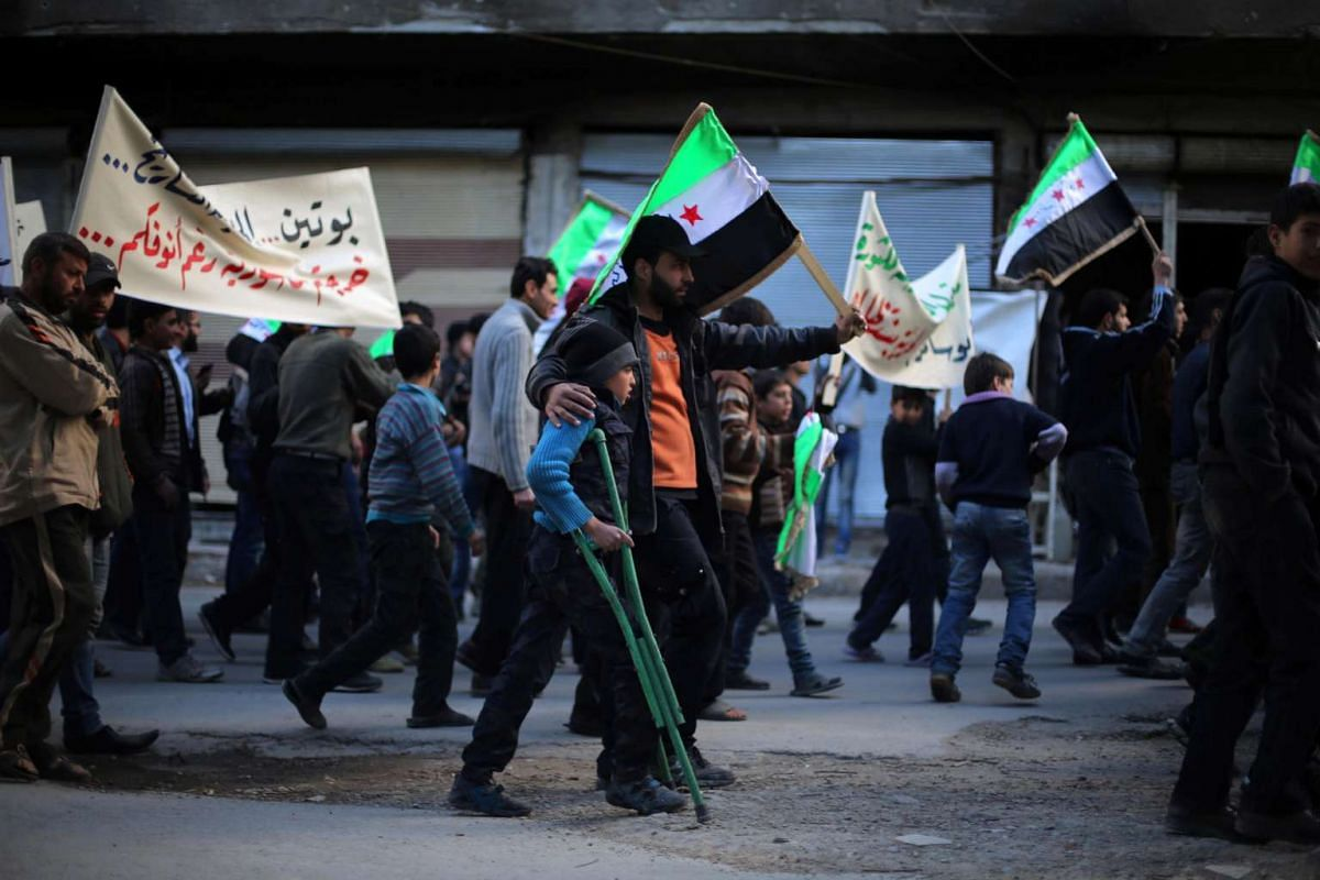 Protesters hold flags and placards during an anti-regime demonstration in the rebel-held town of Saqba, on the outskirts of the Syrian capital Damascus, on March 16, 2016. PHOTO: AFP