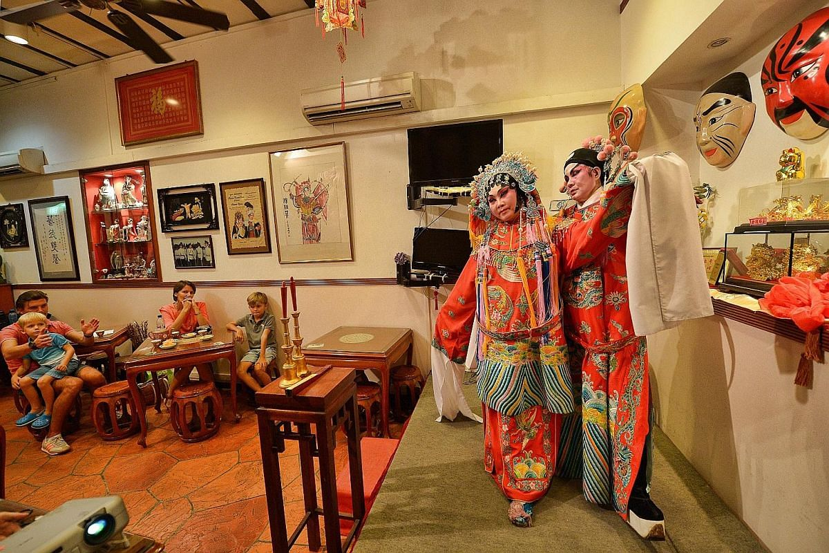 Fastening her skirt, Madam See Too gets ready in a makeshift dressing area in the three-storey Opera Tea House in Smith Street. To date, she has given nearly 2000 performances. (From left) Ms Frances Wong, Mr Henry Wong and Mr Gary Ong practising a d