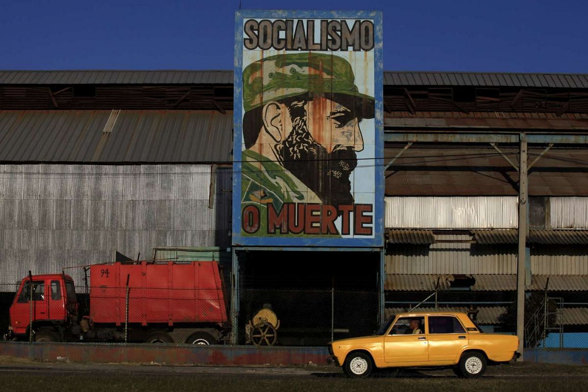 A man drives a car past a billboard with the image of former Cuban leader Fidel Castro in Havana, on March 7, 2016.