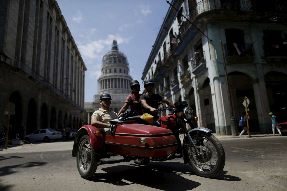 Tourists ride in a vintage motorcycle with a sidecar in downtown Havana, on March 16, 2016.