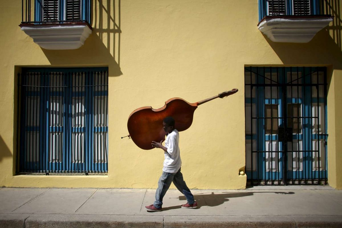 Musician Frilal Ortiz carries a cello in downtown Havana, on March 16, 2016.