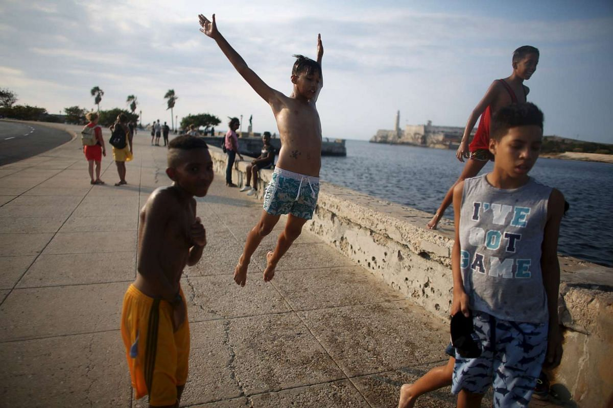 Alberto Echeverria (centre) plays at the seafront Malecon in Havana, on March 16, 2016.