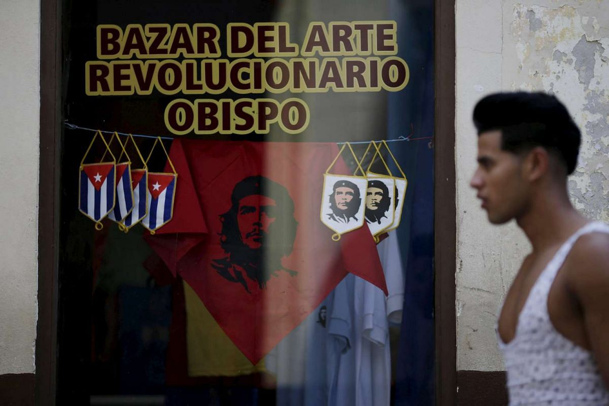 "A man walks pass a shop with souvenirs of revolutionary hero Ernesto ""Che"" Guevara in Havana, on March 16, 2016."