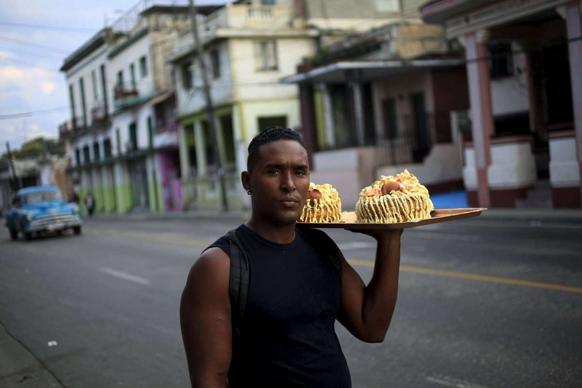 Private vendor Humberto  offers cakes for sale on a street in Havana, on Feb 29, 2016.