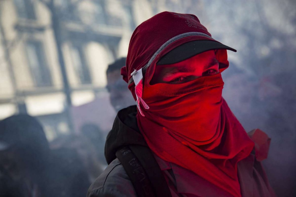 A student is illuminated by a flare as he takes part in a demonstration against the government's controversial labour reform, in Paris, France, on March 17,  2016. PHOTO: EPA