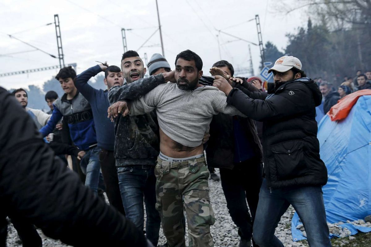 Refugees dragging another refugee to the police, accusing him of abusing a young girl, at a makeshift camp at the Greek-Macedonian border near the village of Idomeni, Greece, on March 17, 2016. PHOTO: REUTERS