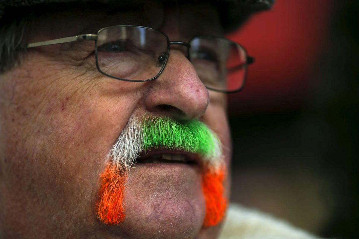 A man watches revellers while they march during the St Patrick's Day parade in New York, on March 17, 2016.