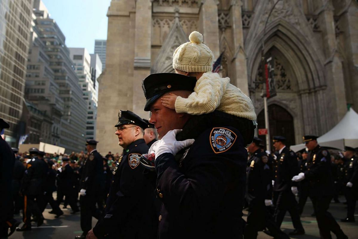 A police officer and his son march in the annual St Patrick's Day parade in New York, on March 17, 2016.