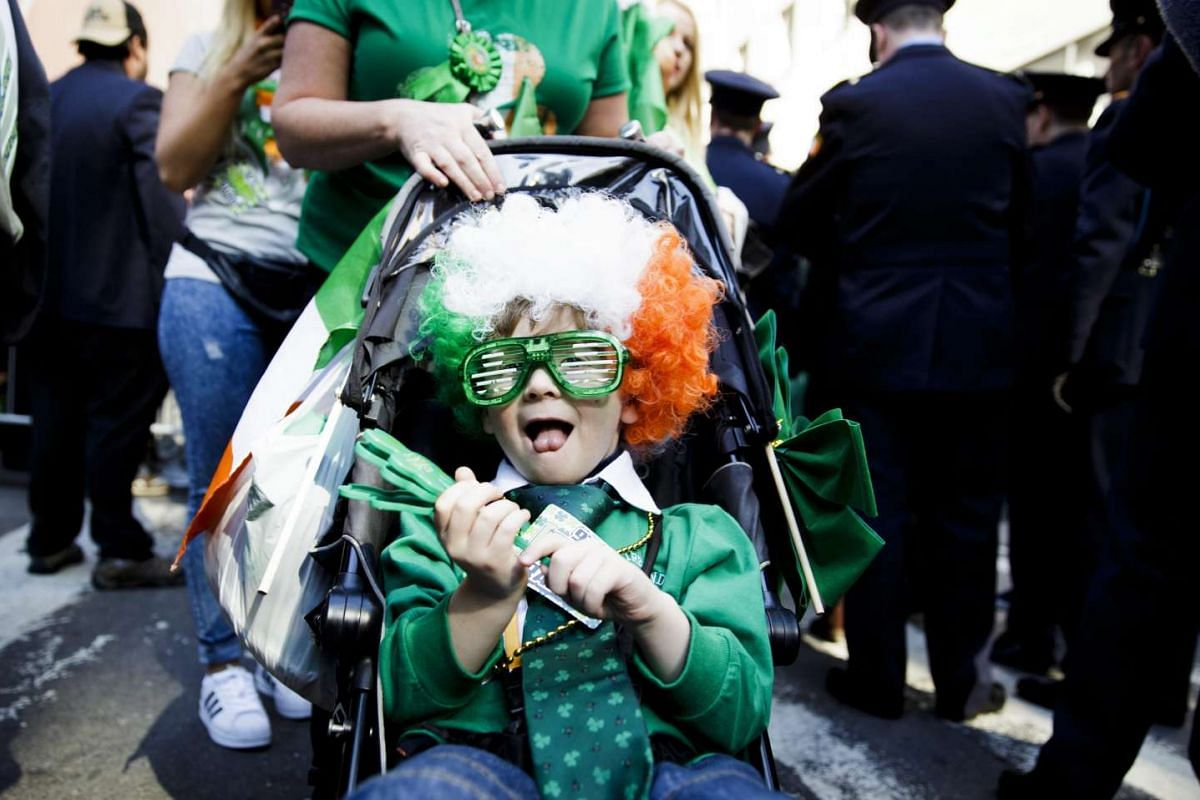 A young boy in a wig and glasses watches the 2016 St Patrick's Day parade in New York, on March 17, 2016.