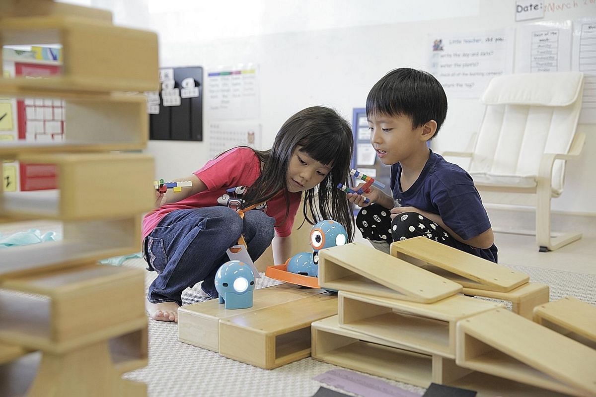 (From far left) Lorraine Tay, four, Chan Xue Jin, three, Evangelista Lee, four, and Ng Dreyen, four, spend at least an hour a day outdoors at Little Village. (From left) Tan En Xi Jolene and Keefe Ryanputra Aditio, both five, playing with robotic toy