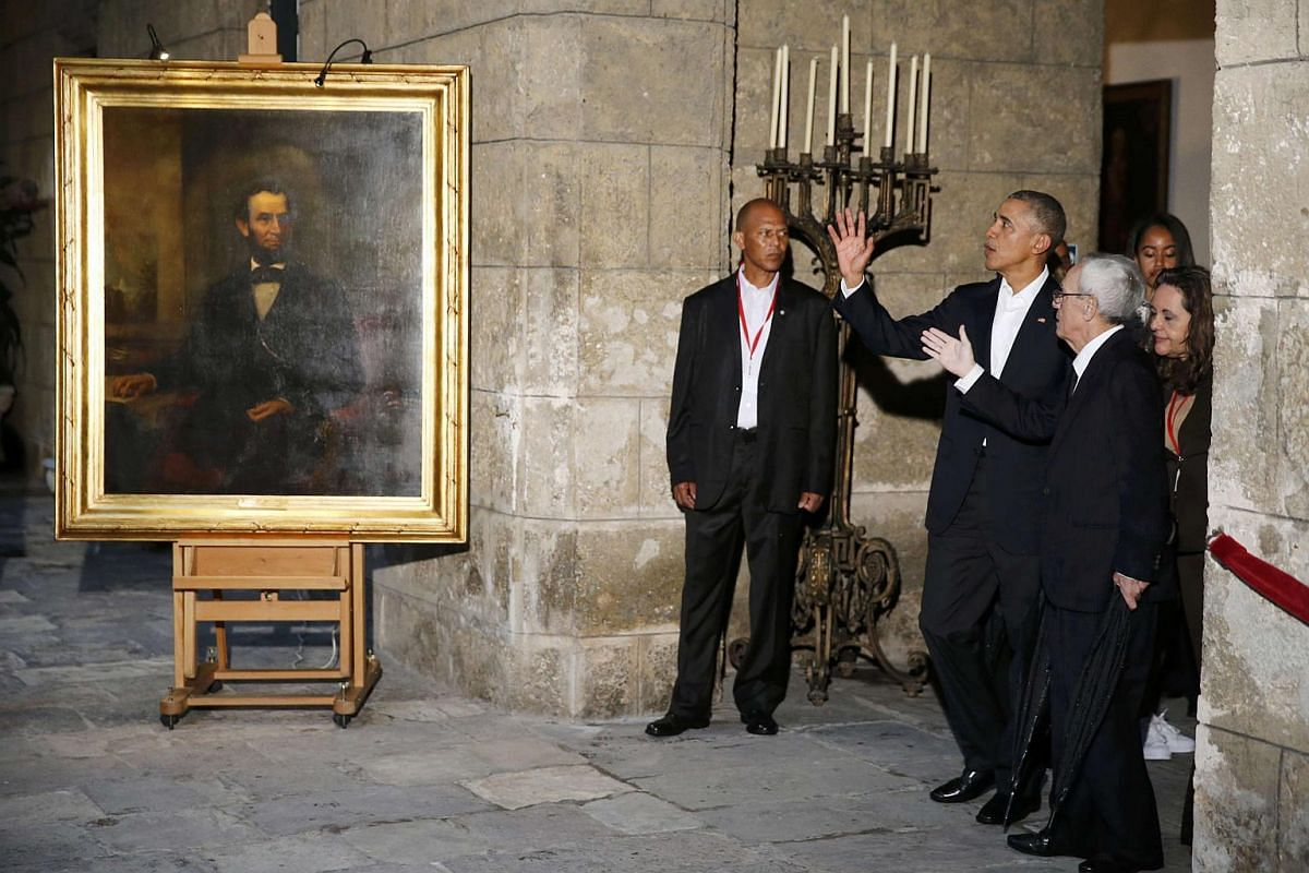 US President Barack Obama standing near a portrait of Abraham Lincoln as he is guided around Old Havana.