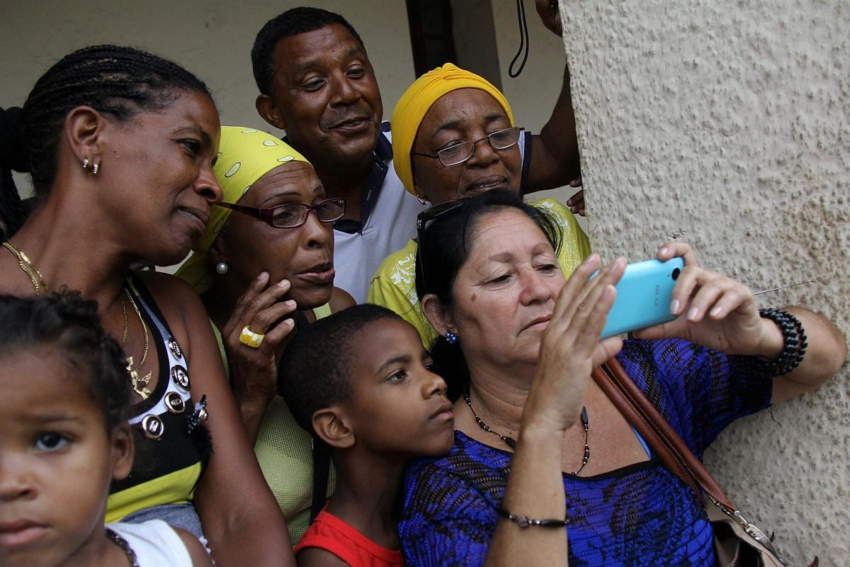 Cubans watching a broadcast of US President Barack Obama's arrival in Havana.