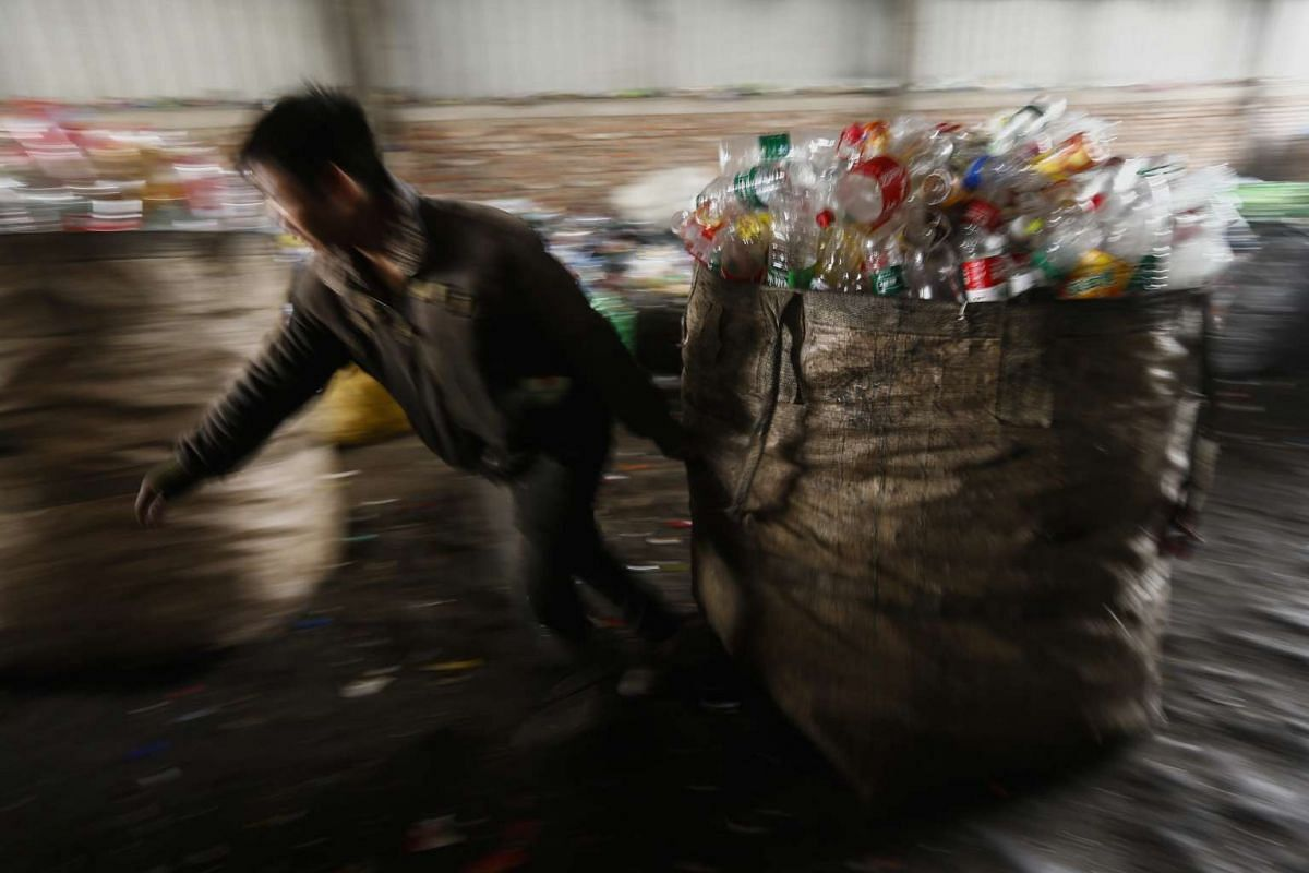 A worker pulls a sack of used plastic bottles at a collection and sorting facility in Beijing, China, on March 15, 2016.
