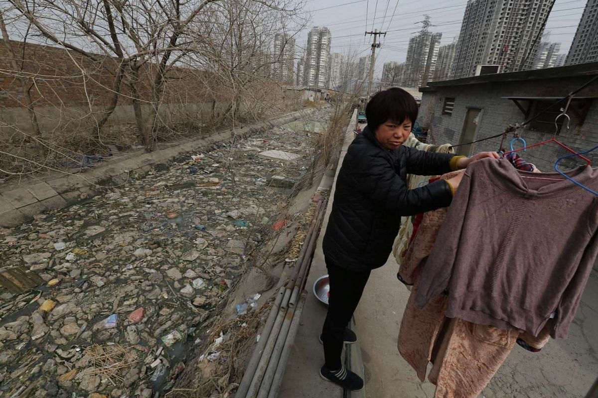 A local resident dries her clothes by a polluted river filled with plastic waste in Beijing, China, on March 19, 2016.