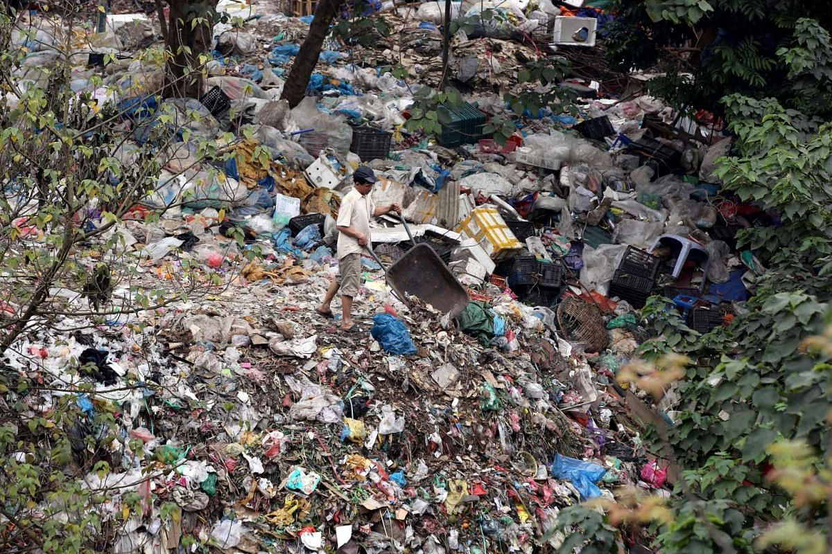 A man dumps garbage at a garbage site in Hanoi, Vietnam, on March 3, 2016.