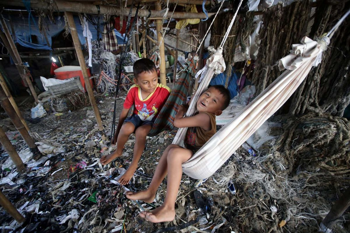 Indonesian boys play swings on a polluted area at a slum in Jakarta, Indonesia, on March 16, 2016.