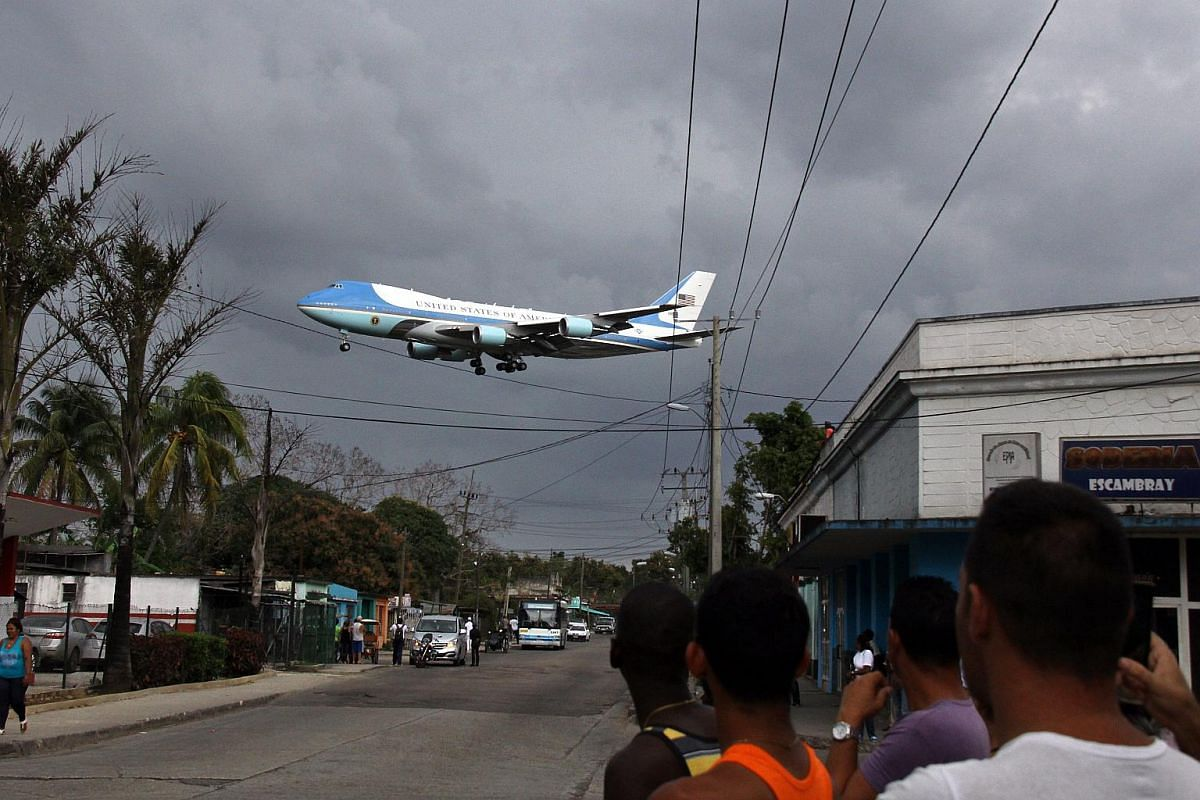 Cuban citizens look as Air Force One lands at Jose Marti Airport in Havana, Cuba, on March 20, 2016.
