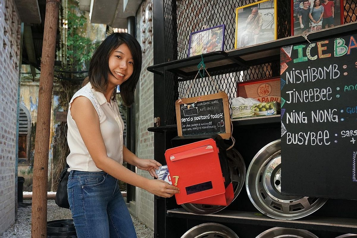 Ms Gladys Tee retrieving a postcard left for her to post out. It is part of her project, in which she makes postcards of the city for visitors, and is aimed at getting people to connect with one another. Ms Rachel Yeow at the Burps & Giggles cafe, wh