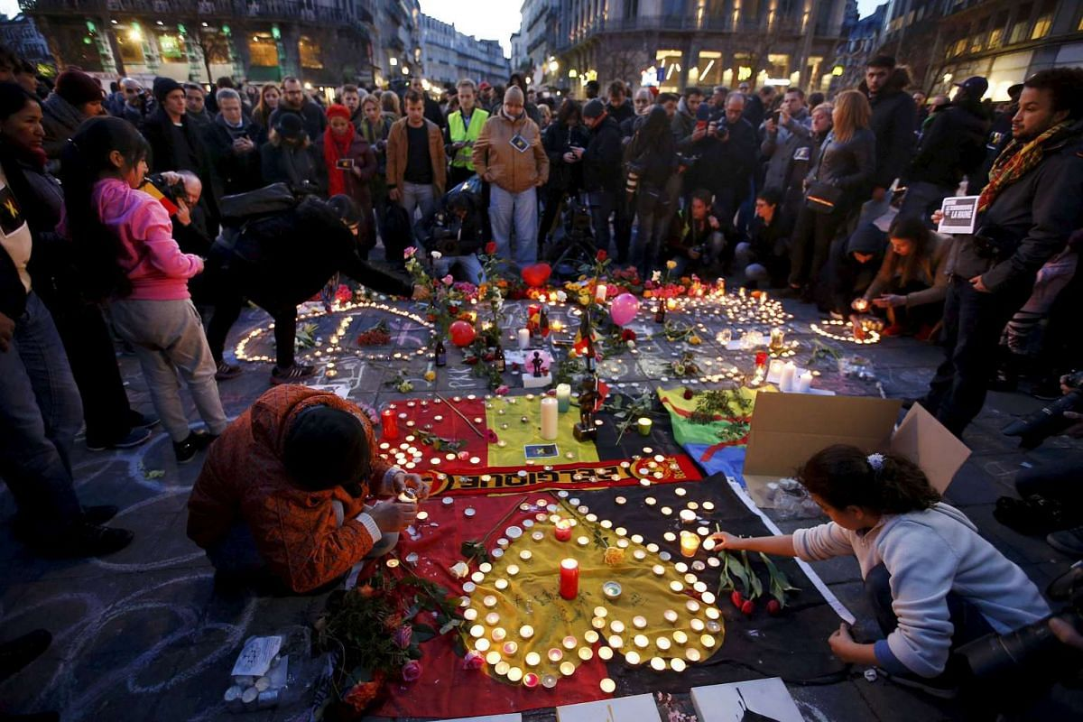 People gather around a memorial in Brussels following bomb attacks in Brussels, Belgium, March 22, 2016. PHOTO: REUTERS