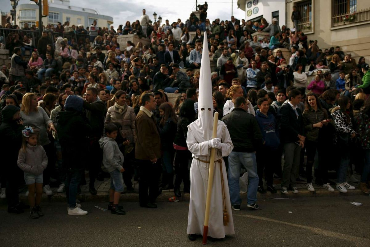 """A penitent of Rocio brotherhood takes part in a procession at """"La tribuna de los pobres"""" (Tribune of the poors) during Holy Week in Malaga, southern Spain, March 22, 2016. PHOTO: REUTERS"""