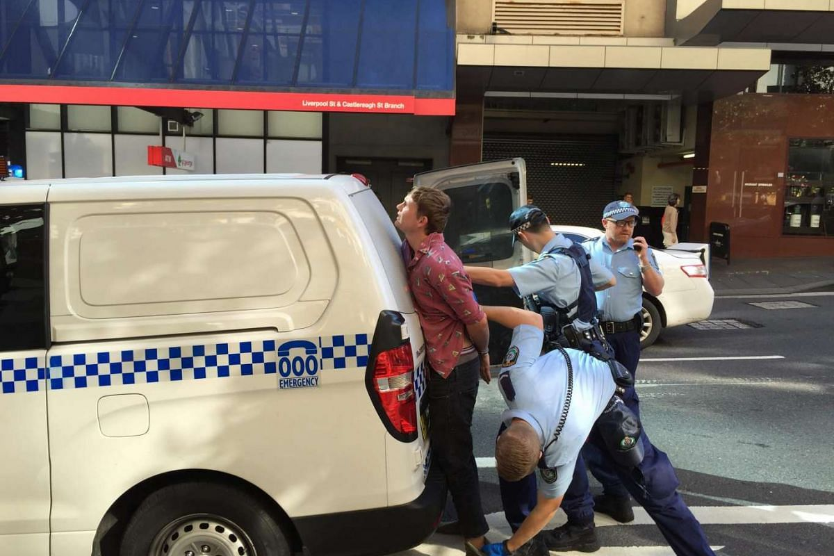 A man is taken away by police after an incident at the Downing Centre Court in Sydney, Australia, March 23, 2016. Police were seen leaving the foyer carrying a machete, a pair of boots and a camera, believed to have belonged to the man. PHOTO: EPA