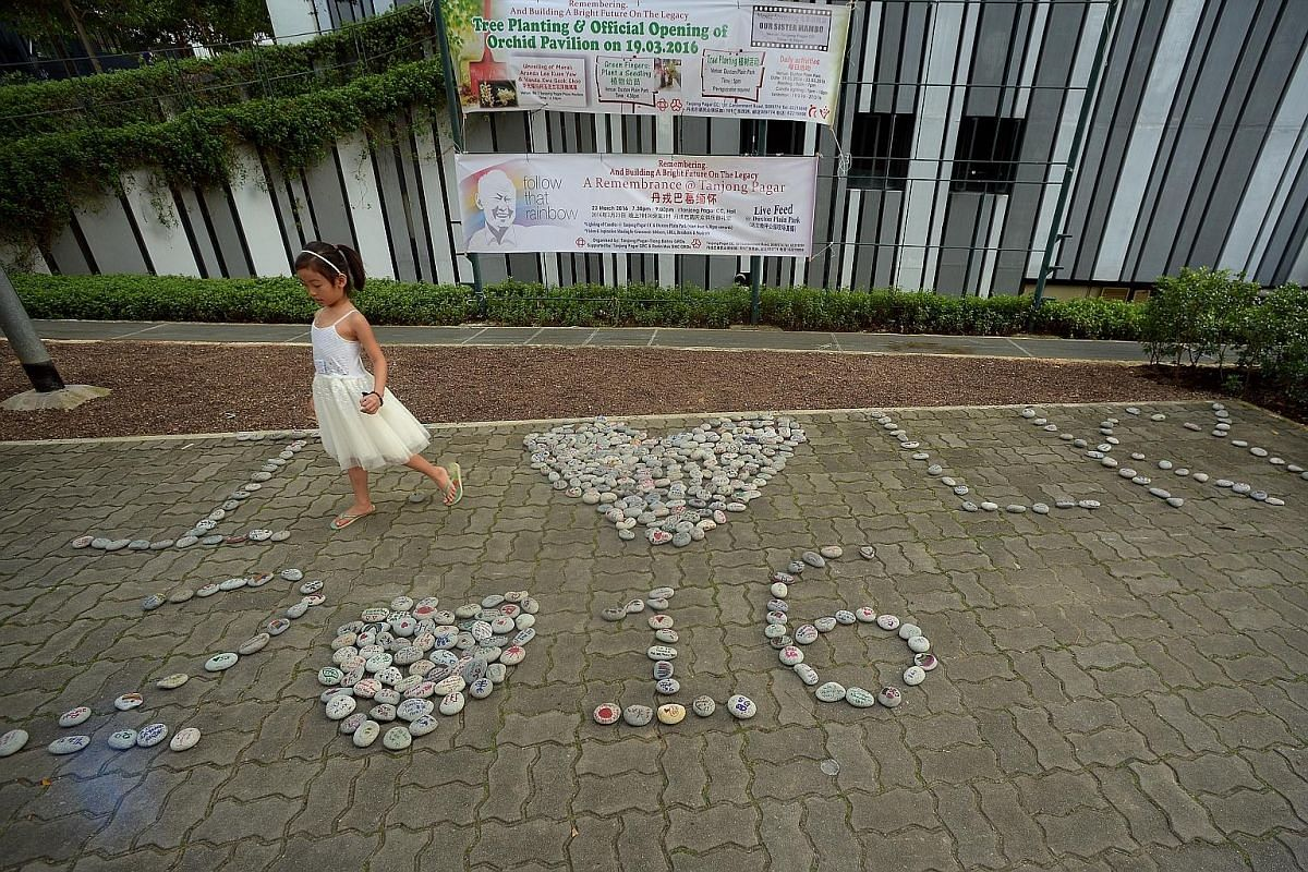 """The writing's on the floor. Georgia Lee, 6, with the pebbles that residents of Tanjong Pagar GRC had arranged outside the Pinnacle@Duxton last Saturday to say: """"I love LKY. 2016."""""""