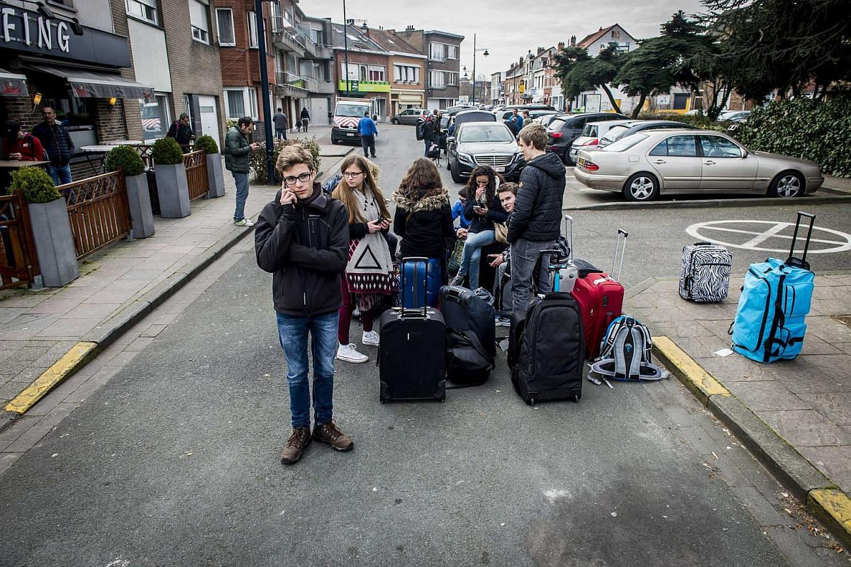 Passengers waiting with their luggage near the Brussels Airport on March 22.