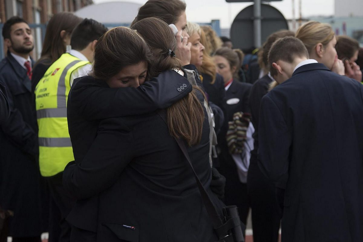 Passengers and airport staff are evacuated from the terminal building after explosions at Brussels Airport on March 22.