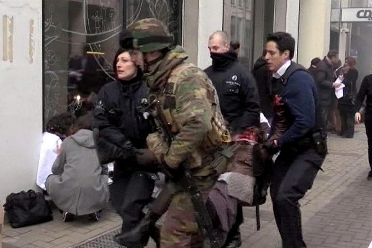 A TV image showing Belgian policemen and a soldier carrying an injured person after an explosion at the Maelbeek station in Brussels on March 22.