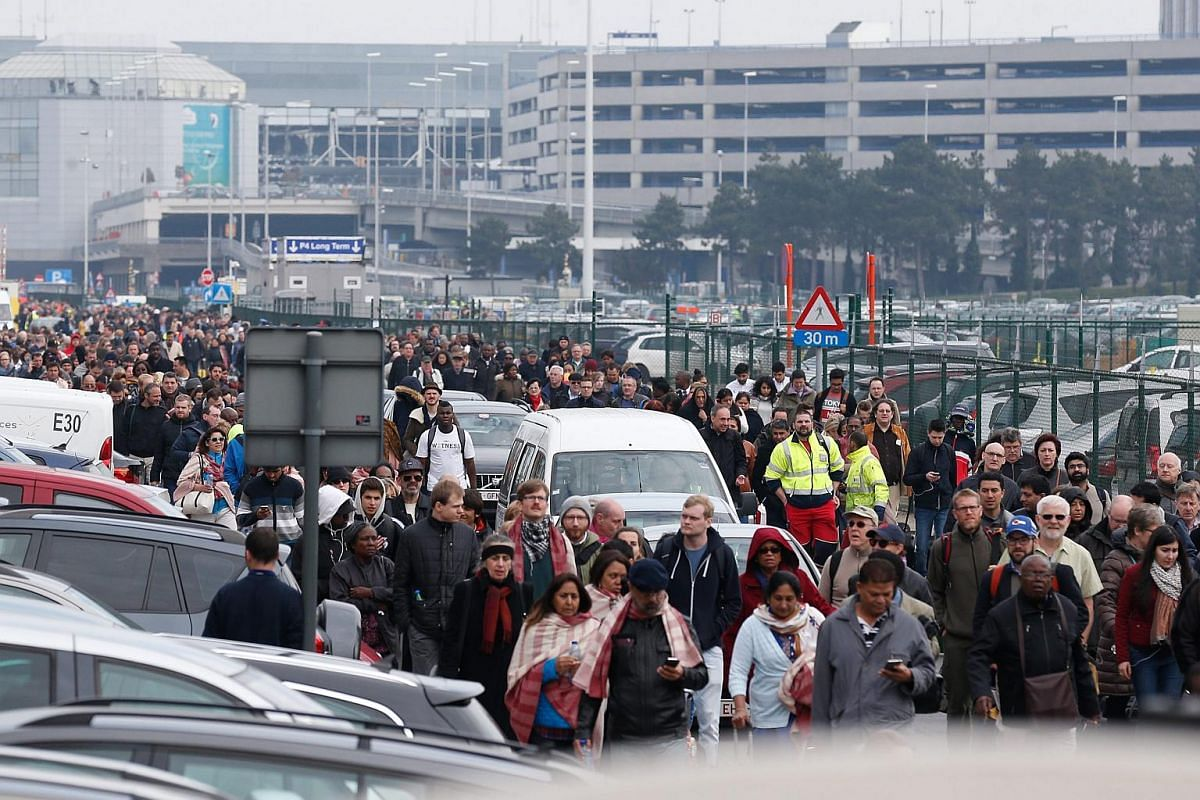 Passengers and airport staff evacuating the Brussels Airport on March 22.