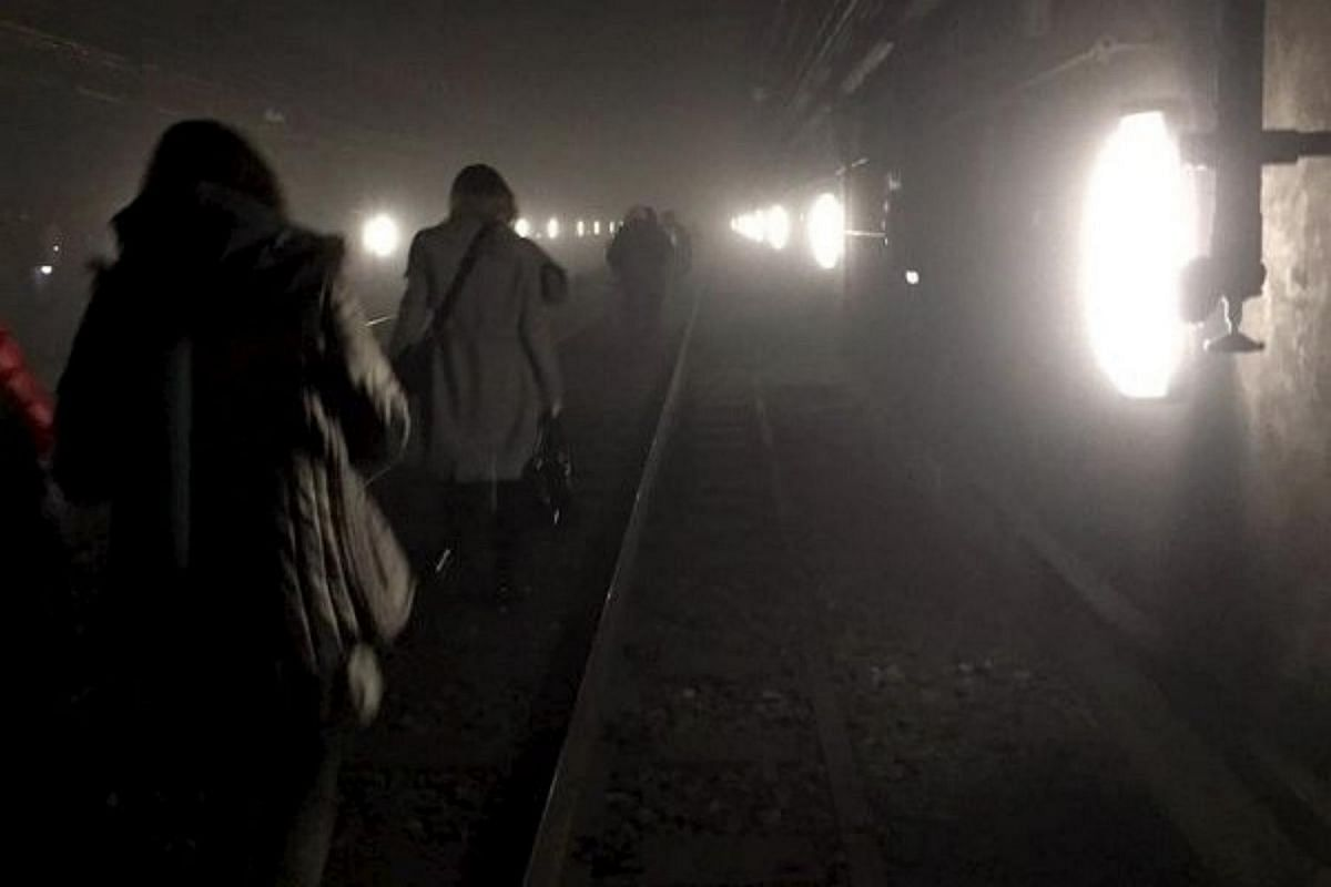 Passengers walking on underground metro tracks after an explosion at Maelbeek station in Brussels on March 22.