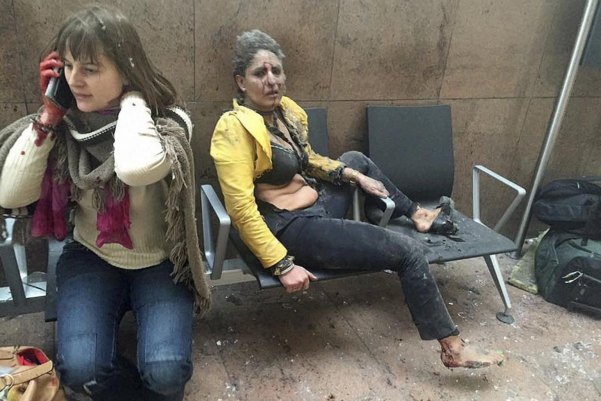 Injured people at the scene of explosions at the Brussels Airport on March 22.