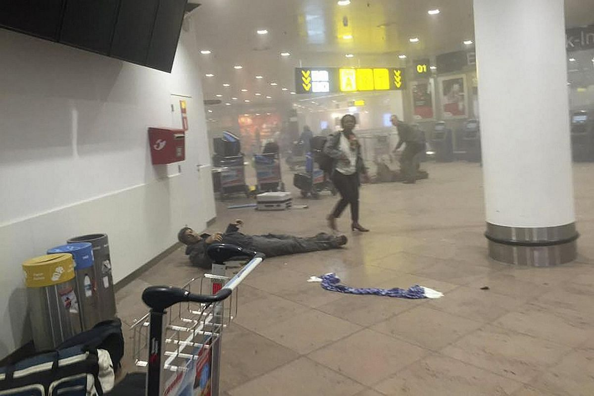 An injured man lying at the scene of explosions at the Brussels Airport on March 22.