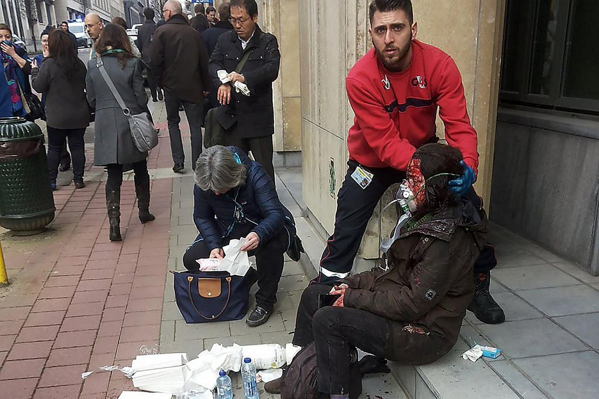 A private security guard helping a wounded woman outside the Maalbeek metro station in Brussels.