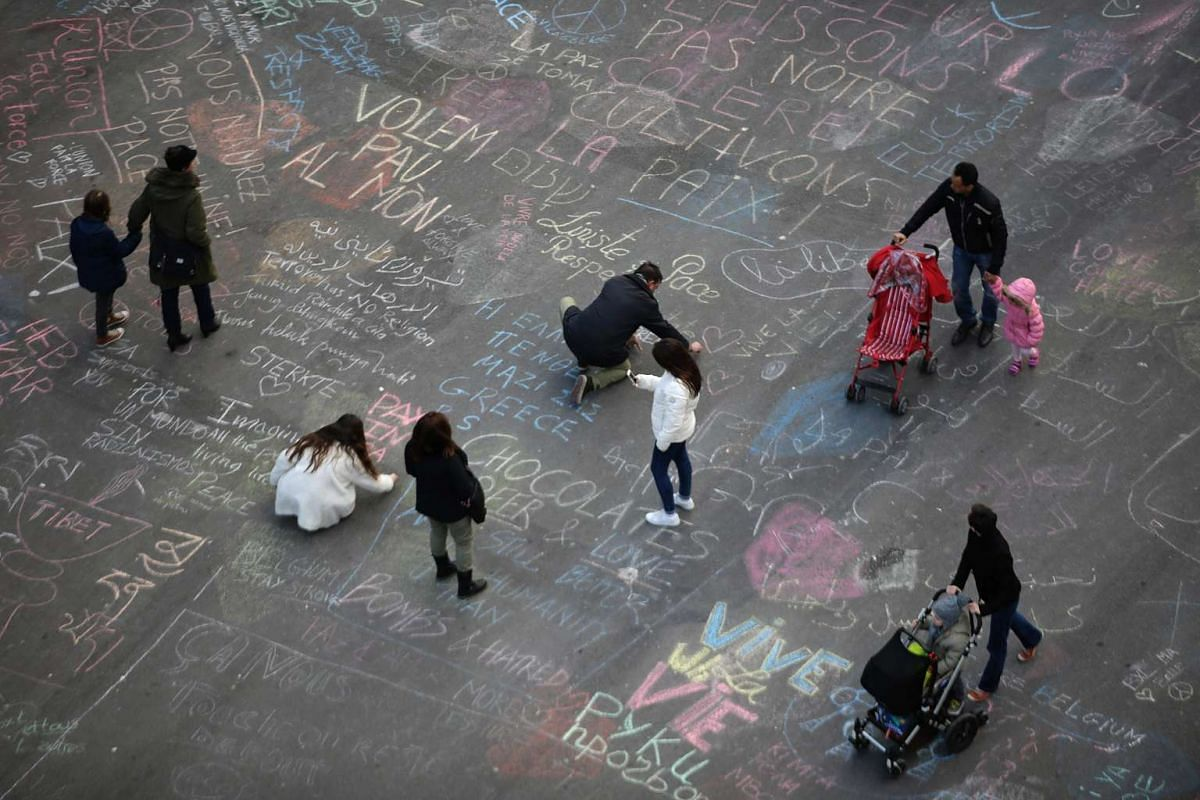 People writing messages on the ground at Place de la Bourse following the attacks in Brussels on March 22.