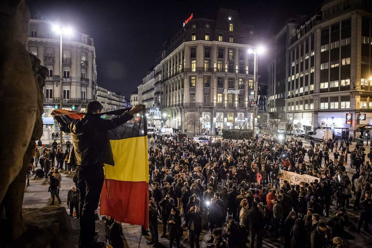 A man holding a Belgian flag at Bourse square in Brussels on March 22.