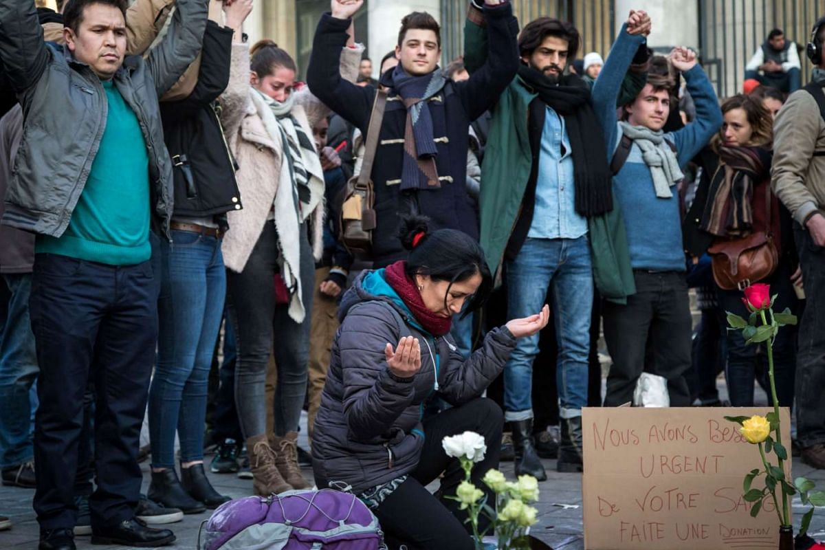 People praying for victims of the Brussels terror attacks at a makeshift memorial in front of the stock exchange at the Place de la Bourse in Brussels on March 22.