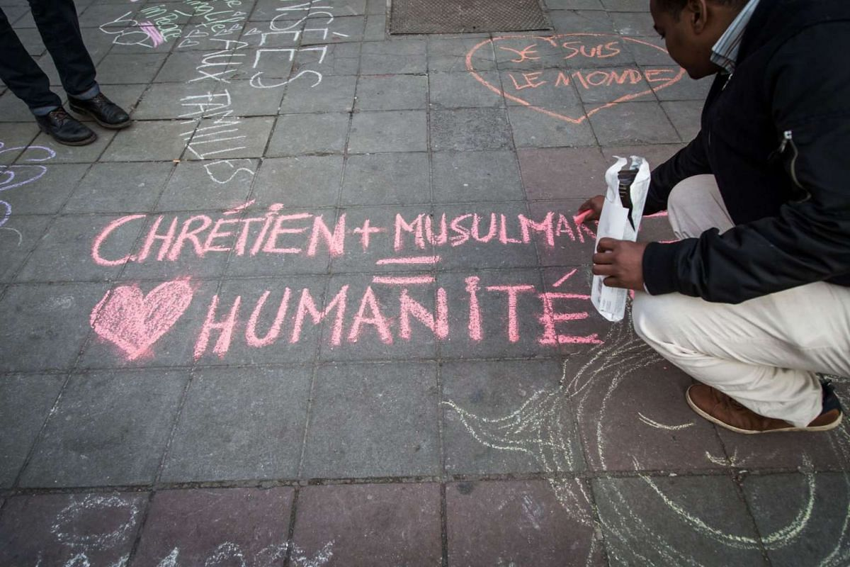 """A man writing """"Christian and Muslim equals humanity"""" on the ground in tribute to victims at a makeshift memorial in front of the stock exchange at the Place de la Bourse in Brussels on March 22."""