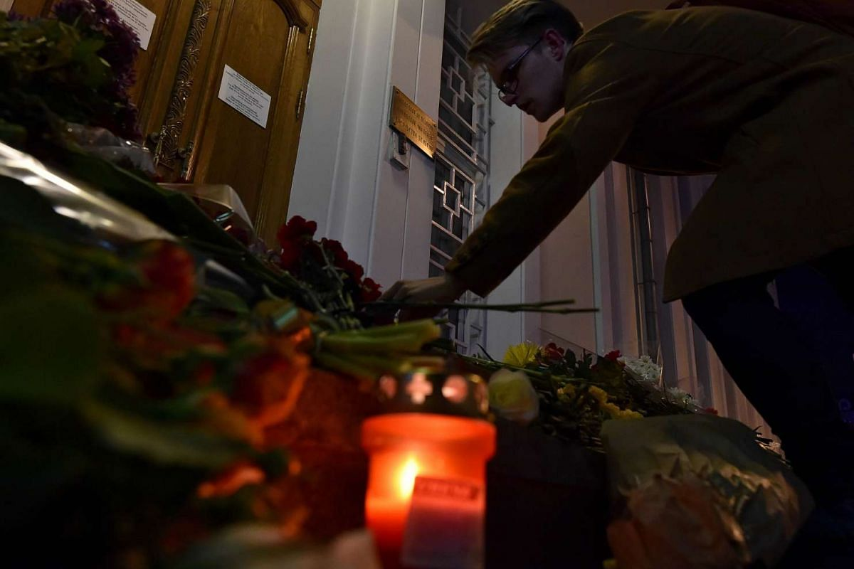 A man placing flowers outside the Belgian embassy in Moscow on March 22, in tribute to the victims of the Brussels attacks.