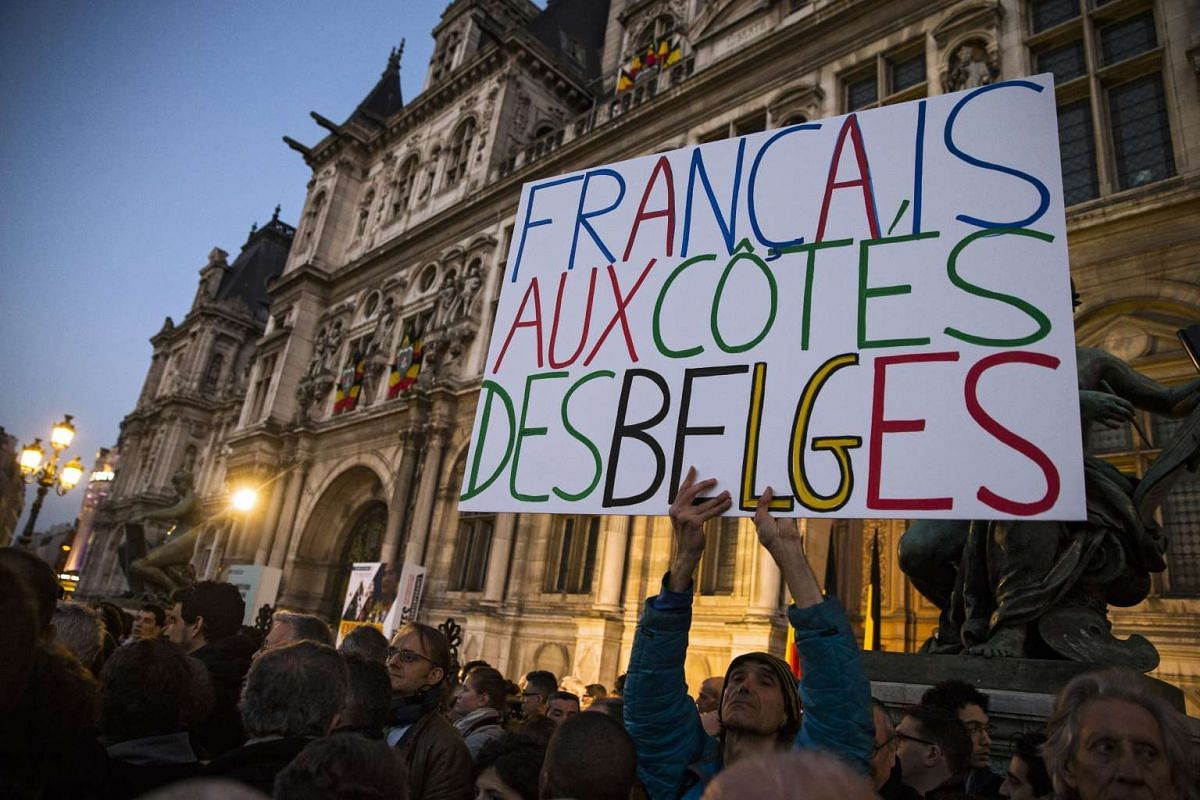"""A man holding a poster stating """"French together with Belgians"""" during a gathering in Paris on March 22."""