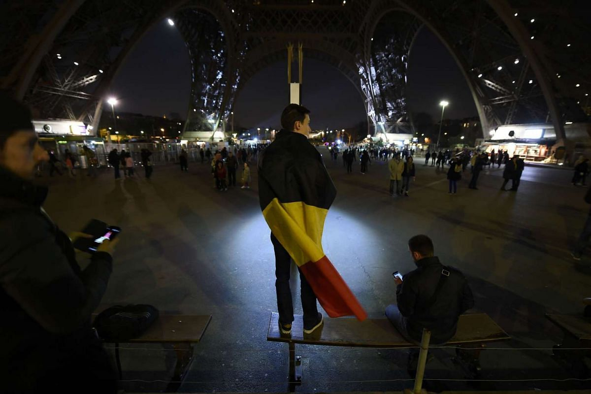 A boy wearing a Belgian flag standing under the Eiffel Tower in Paris illuminated in colours of the Belgian flag in tribute to the victims of the Brussels attacks on March 22.