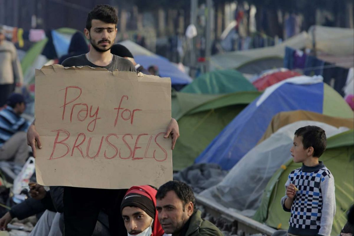 A migrant holding a sign in support for the victims of the terror attacks in Brussels, at a refugee camp on the Greek-Macedonian border, on March 22.