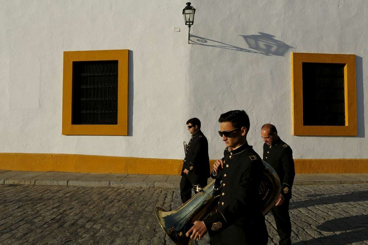 Musicians of El Carmen band walk before taking part in the El Baratillo procession during Holy Week in the Andalusian capital of Seville, Spain, on March 23, 2016.