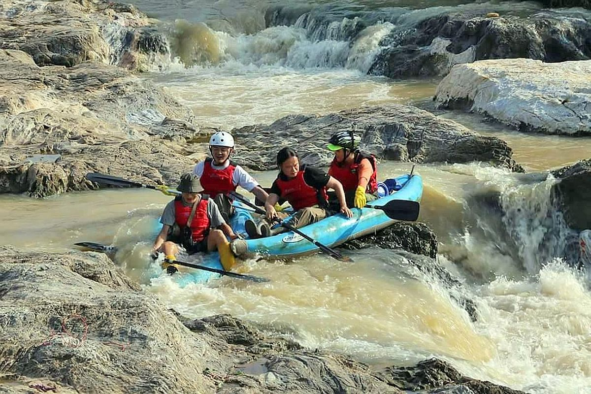 Mr Lim (above, front) and Dr Ong (second from left) kayaking down the Klang river, where they were surprised by rapids not far from downtown Kuala Lumpur.