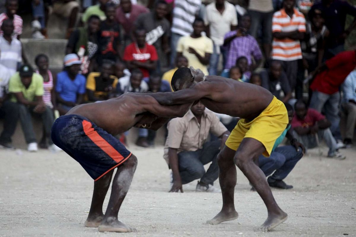 Men fight during an amateur wrestling competition in Port-au-Prince, Haiti, on March 26, 2016. The event is held during Easter in Haiti.