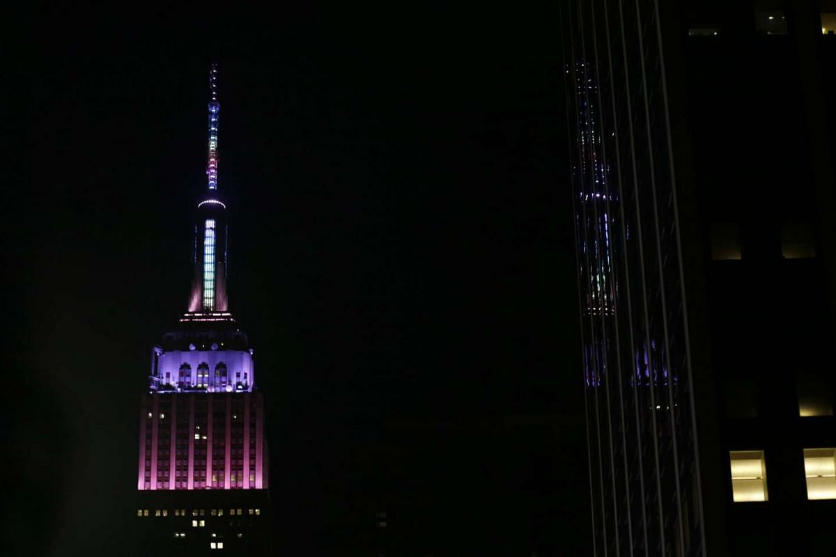 The Empire State Building is seen lit in Easter colours in New York, on Mach 26, 2016.