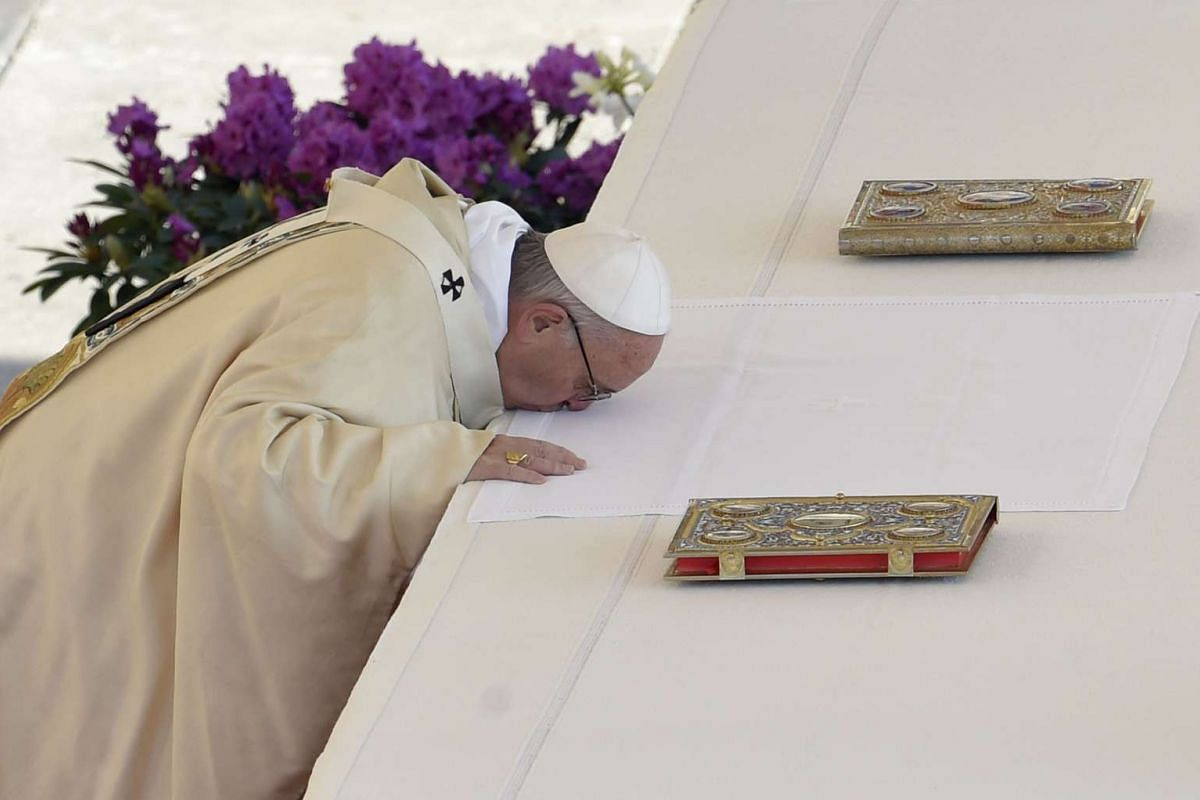 Pope Francis kisses the altar during the Easter Sunday mass on March 27, 2016 at St Peter's square in Vatican City. Christians around the world are marking the Holy Week, commemorating the crucifixion of Jesus Christ, leading up to his resurrection o