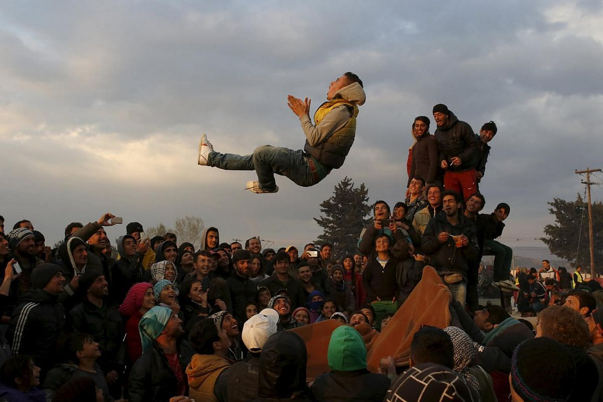 Migrants and refugees singing and dancing during a party at a makeshift camp at the Greek-Macedonian border near the village of Idomeni, Greece, on March 27, 2016.